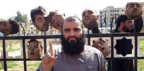 Un islamo-fasciste posant devant les têtes de chrétiens décapités en Irak et exhibées sur 600 m dans une avenue de Mossoul.