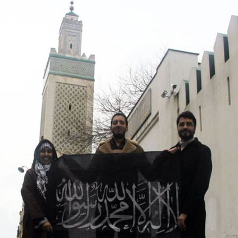 Yassine Ayari en juillet 2013 devant la grande mosquée de Paris, en compagnie d'islamistes tunisiens, montrant l'étendard d'Al-Qaïda récemment repris par Daech.